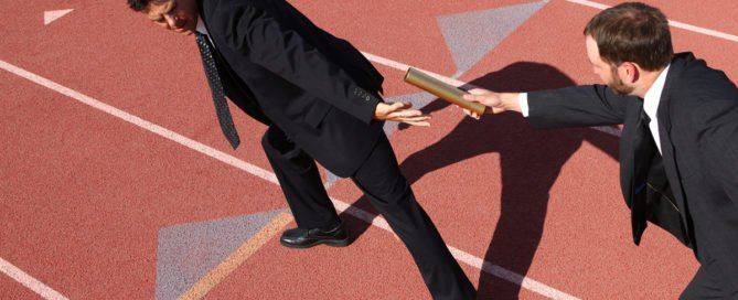 Success in Succession-Businessmen passing the baton in a track relay