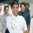 Nesso-Character-istic-confident-businesswoman-Multiethnic businesswoman standing with her colleagues in backgr
