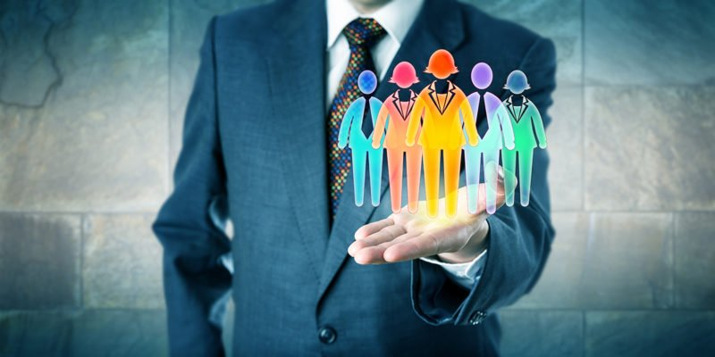Nesso-Cultivating Belonging-Diversity-Inclusion-146850122White collar manager presenting a work team of five multicolored worker icons in open palm of his left hand. Business concept for team building diversity inclusion culture and staffing solutions.